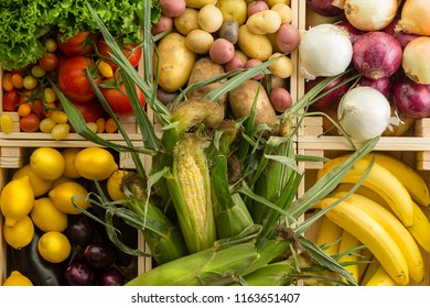 Fresh healthy assorted fruit and vegetables background displayed together in wooden boxes wooden table at an organic farmers market in a full frame close up view from above