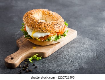 Fresh healthy bagel sandwich with salmon, ricotta and soft egg on vintage chopping board on stone kitchen table background