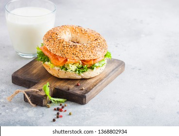 Fresh healthy bagel sandwich with salmon, ricotta and lettuce on vintage chopping board on stone kitchen table background.