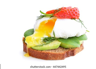 Fresh Healthy Breakfast:Poached egg on piece of rye bread with Avocado slices,Spinach and Strawberry .