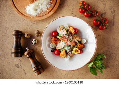Fresh healthy caesar salad with chiken on stone table. Top view