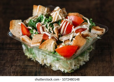 Fresh healthy caesar salad in disposable container box on wooden table.