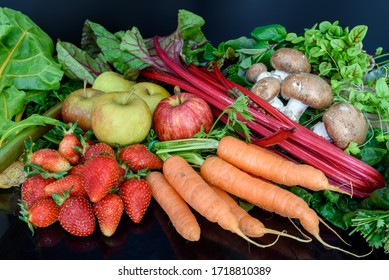 Fresh healthy colorful composition of assorted raw organic seasonal fruits and vegetables isolated on dark background.