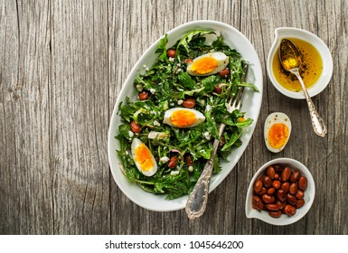Fresh healthy dandelion salad with eggs and beans overhead shoot