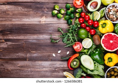 Fresh and healthy food. Avocabo, brussel sprouts, cucumbers, red, yellow and green peppers, chili pepper, cherrie tomatoes, lemon, kiwi, apples, pomegranate, lime, blue onion, spinach and salad lie
