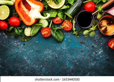 Fresh healthy food cooking or salad making ingredients on dark background with rustic wooden board. Diet or vegetarian food concept. Top view, copy space