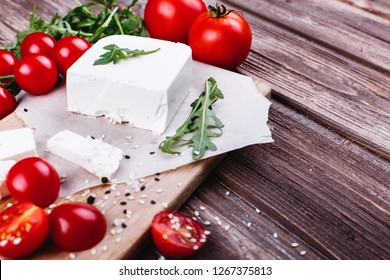 Fresh and healthy food. Delicious Italian dinner. Fresh cheese served on wooden board with arugula