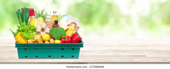 Fresh healthy food and vegetables from grocery store in tray box on wood tabletop in blur green natural bokeh banner background with copy space