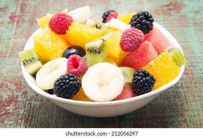 fresh healthy fruit salad on wooden background