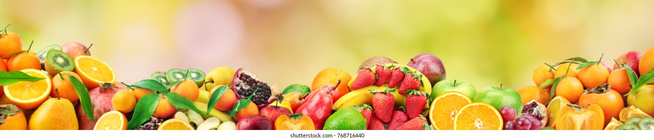 Fresh healthy fruits on natural blurred multicolored background. Free space for text.