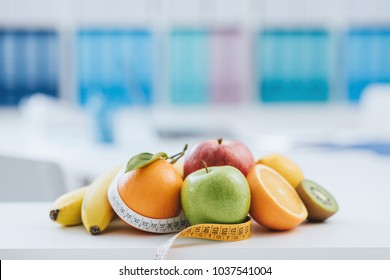 Fresh healthy fruits and tape measure in the nutritionist office: dieting and weight loss concept