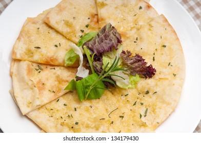 fresh healthy garlic pita bread pizza with salad on top