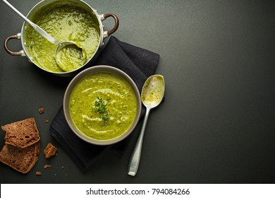 Fresh healthy green soup on black background overhead shoot.