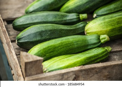 Fresh healthy green zucchini courgettes cucumber in brown wooden box on the marketplace, the pantone color of the year 2017, Greenery 15-0343