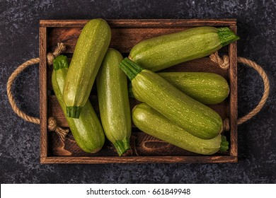 Fresh healthy green zucchini courgettes in brown wooden box, top view.