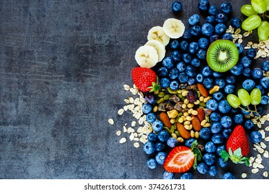 Fresh healthy ingredients (oat flakes, banana, berries with yogurt and seeds) for breakfast or smoothie on dark vintage background - Healthy food, Diet, Detox, Clean Eating or Vegetarian concept.