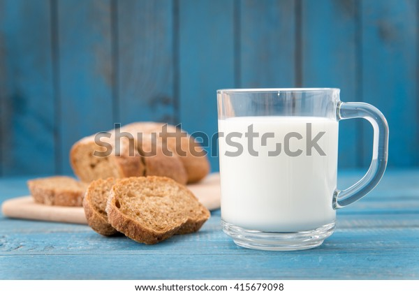 fresh healthy milk and bread on a wooden rustic table