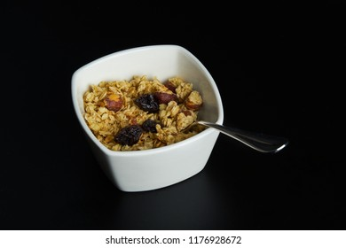 Fresh healthy musli with spoon on black background