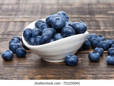 Fresh healthy organic blueberry in white bowl on wooden background