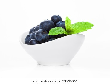 Fresh healthy organic blueberry in white bowl with mint leaf on white background