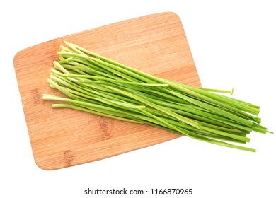 Fresh healthy organic green vegetable garlic chives, chinese chive bunch, green herb on a wooden cutting board isolated on white background with clipping path.
