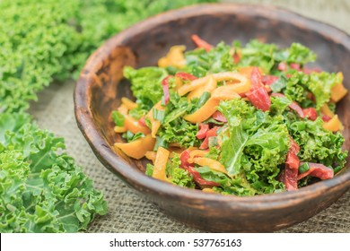 Fresh healthy raw nutritional salad with organic curly kale greens and multicolored bell peppers on wooden background top view with space for text. Healthy food concept. Natural Ceramic tableware use.