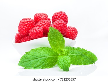 Fresh healthy red raspberries in white bowl with mint leaf on white background.