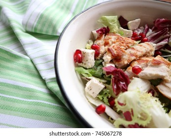Fresh healthy salad with grilled chicken, feta cheese, salad mix, pomegranate seeds and olive oil. Clean eating, healthy living. Wooden background.
