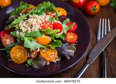 Fresh healthy salad with quinoa, cherry tomatoes and mixed greens (arugula, mesclun, mache) on wood background close up. Food and health. Superfood.