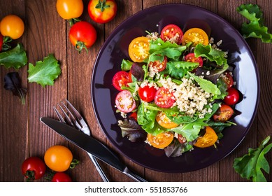Fresh healthy salad with quinoa, cherry tomatoes and mixed greens,arugula, mesclun, mache, on wood background top view. Food and health. Superfood meal. Clean eating. Healthy lifestyle