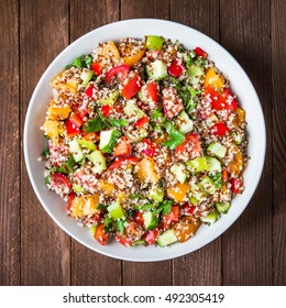Fresh healthy salad with quinoa, colorful tomatoes, sweet pepper, cucumber and parsley on wooden background top view. Food and health. Superfood meal.