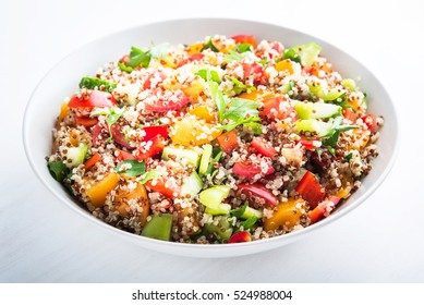 Fresh healthy salad with quinoa, colorful tomatoes, sweet pepper, cucumber and parsley on white wooden background close up. Food and health. Superfood meal.