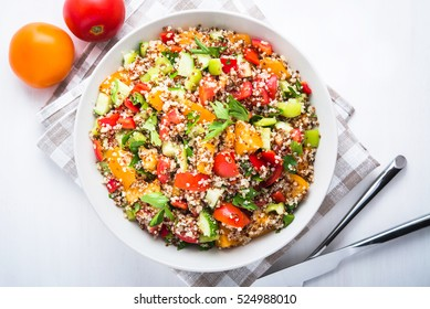 Fresh healthy salad with quinoa, colorful tomatoes, sweet pepper, cucumber and parsley on white wooden background top view. Food and health. Superfood meal.