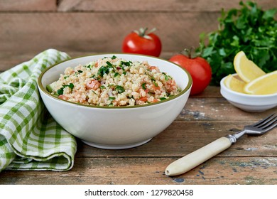 Fresh healthy salad with quinoa, tomatoes, cucumber and parsley on wooden background. Healthy, diet, vegetarian food concept. Flat lay