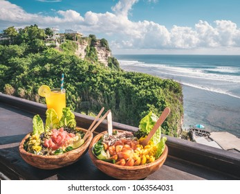 Fresh healthy salads with orange juice with an amazing view over the ocean and rocks in Uluwatu, Bali, Indonesia. Healthy food concept.
