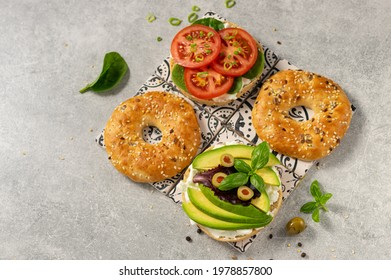 Fresh healthy sandwiches with seeded bagel, slad  and cotage cheese on grey