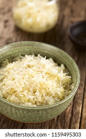Fresh healthy sauerkraut in bowl with jar in the back, photographed on rustic wood (Selective Focus, Focus one third into the image)