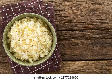 Fresh healthy sauerkraut in bowl, photographed overhead on rustic wood with copy space on the side (Selective Focus, Focus on the sauerkraut)