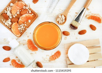 Fresh and healthy skincare product homemade from bright juicy orange tangerine. Top view natural ingredients white table preparing beauty remedy- citrus fruit, cosmetic bottles, almond nuts scattered