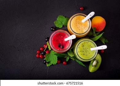 Fresh healthy smoothies from different berries on a dark background. Diet menu. Proper nutrition. Flat lay. Top view.