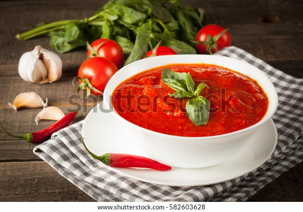 Fresh, healthy tomato soup with basil, pepper, garlic, tomatoes and bread on wooden background. Spanish gazpacho soup.