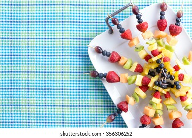 Fresh healthy tropical fruit shish kebabs arranged neatly on a tray placed on a picnic table with a blue checked design and copy space, viewed from above