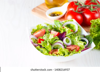 Fresh healthy vegetable salad made of cherry tomato, ruccola, arugula, feta, olives, cucumbers, onion and spices. Greek, Caesar salad in a  bowl on wooden background. Healthy organic diet food concept