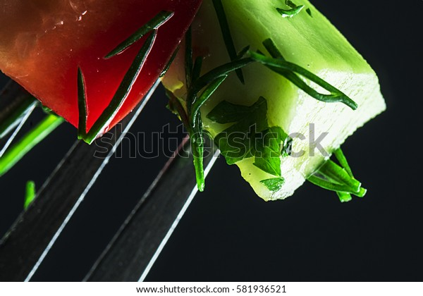Fresh, healthy vegetables on a fork, close-up. Dark background. Focus on vegetables