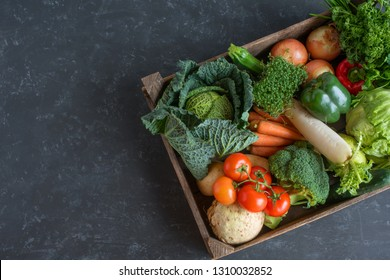 Fresh healthy vegetables selection in a wooden box on a slate plate