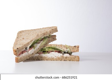 A fresh, healthy wholegrain bread chicken salad sandwich sliced into triangles and stacked on a plain white background with copy space.