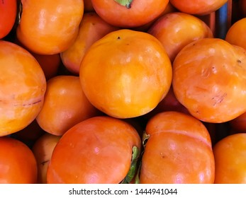 Fresh heap of persimmons as organic background