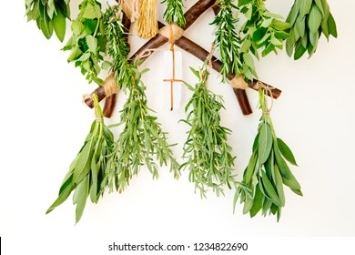 Fresh Herb bundles hanging with selenite crystal on rustic wooden herb dryer on white background