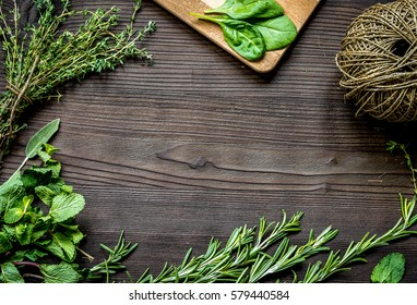 fresh herb frame on dark wooden background top view