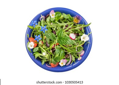 Fresh herb salad with leafy greens and nasturtium flowers served in a blue ceramic bowl